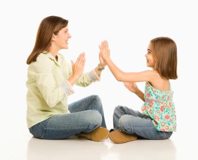 Mother and daughter playing pattycake