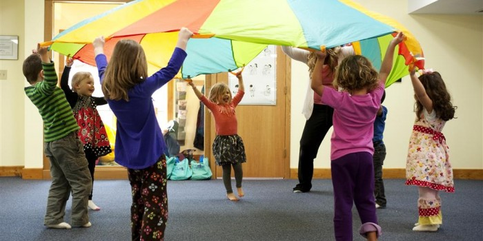 Children using parachute for a circle dance